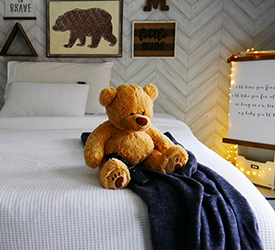 A teddy bear sitting on a Tempur-Pedic mattress