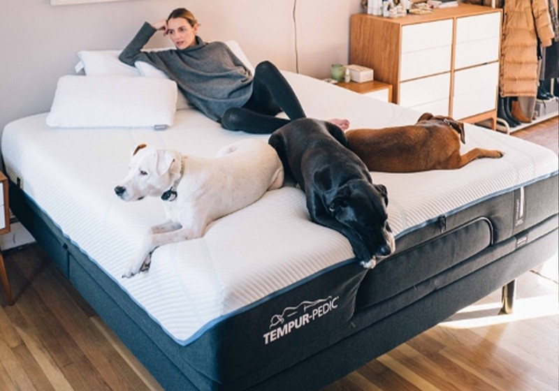 A woman reclining on her Tempur-Pedic mattress with her three dogs