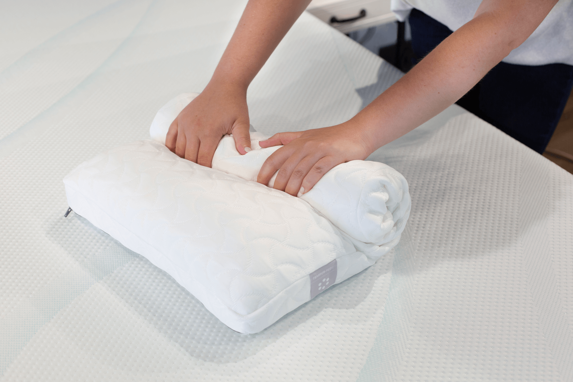 A Tempur-Cloud pillow being rolled up for easy packing