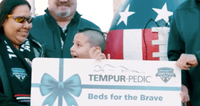 An image of a group of people holding a check being presented to Beds for the brave