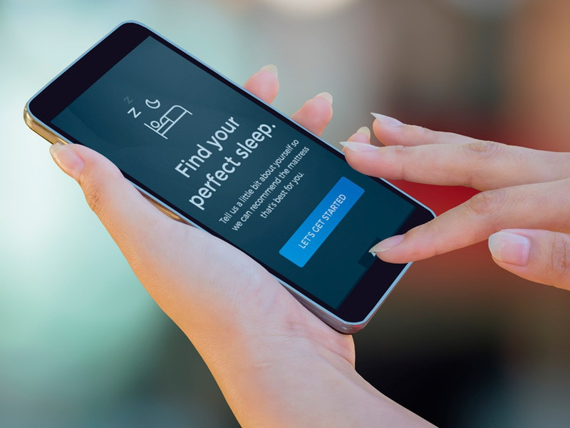 "Hands holding phone with text visible that states ""find your perfect sleep"""