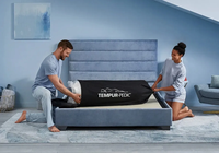 A joyous couple unbagging the tempur-cloud mattress-in-bag