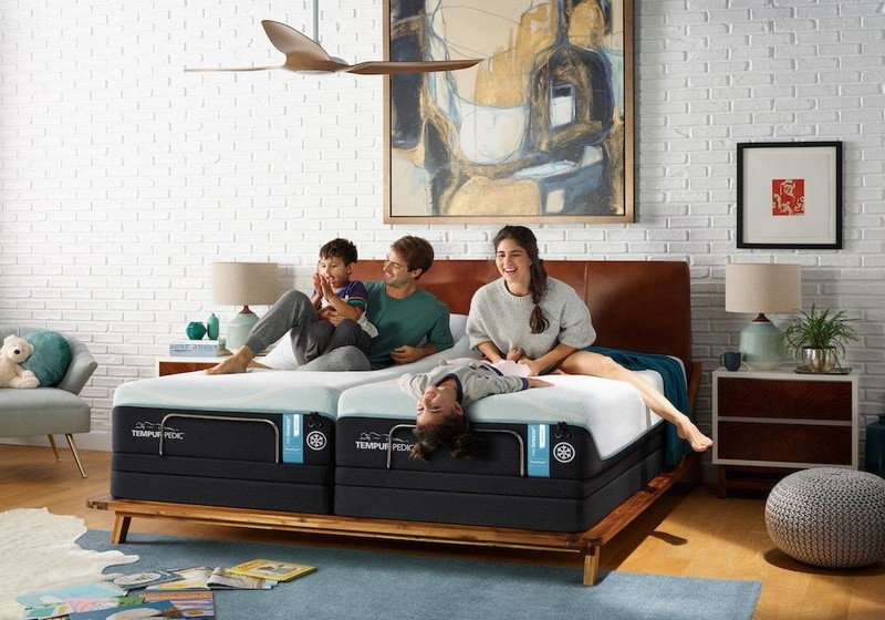 family of four sitting on mattress