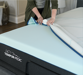 A cover being removed from a Tempur_pedic mattress