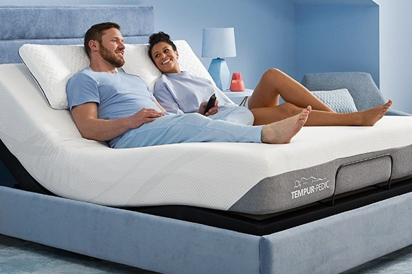 A couple on a Tempur-Pedic mattress enjoying the Zero Gravity Preset feature