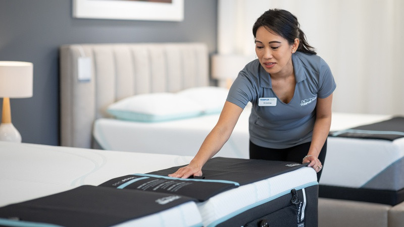 A store associate straightening the bedding on a mattress