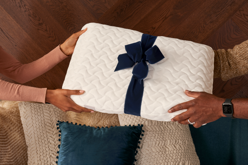 Image of two sets of hands holding tempur cloud pillow with blue ribbon.png