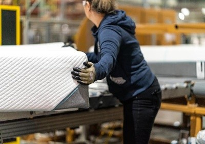 woman grabbing mattress in a factory