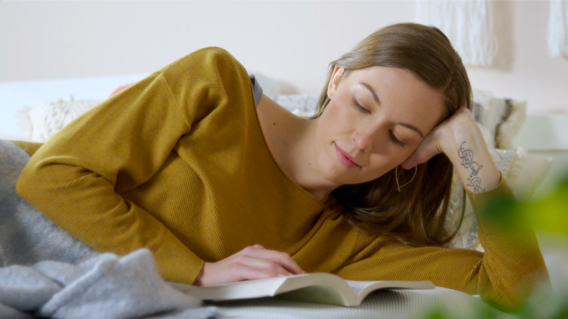 a woman laying on mattress reading
