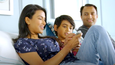 Tempur-Pedic sleepers Rebekah and Raj sitting on their bed with their son
