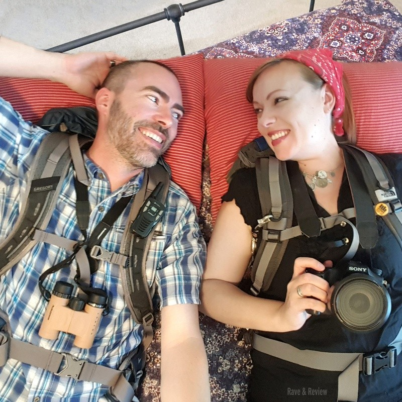 Rave and Review Blog image of woman and man lying on mattress while holding cameras and smiling