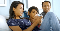 A family of 3 sitting on a mattress with an adjustable base