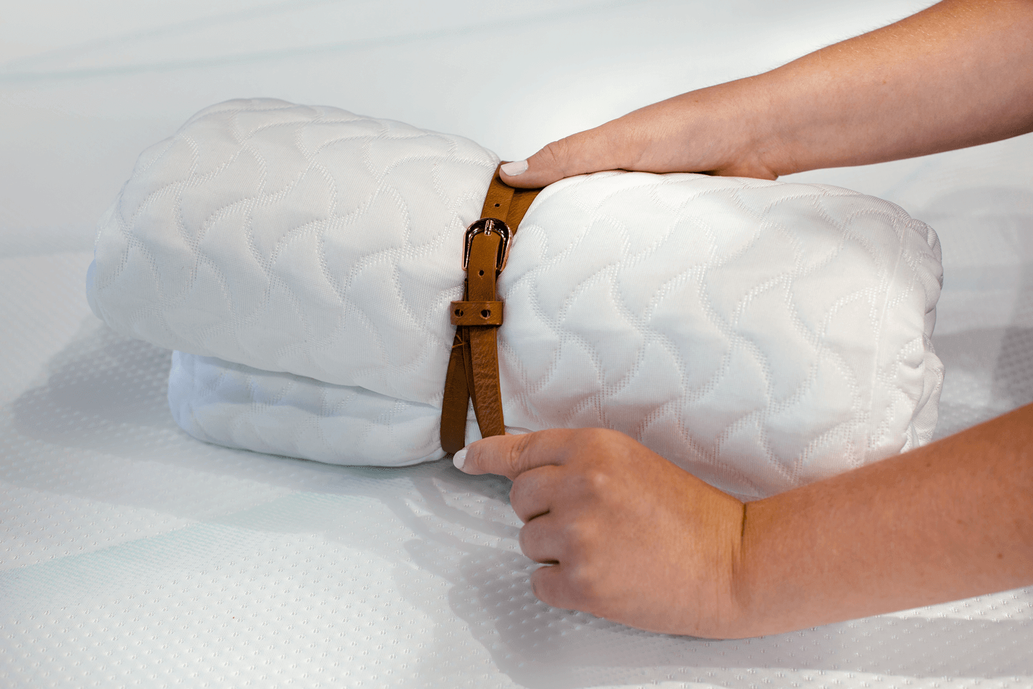 A rolled Tempur-Cloud pillow being secured with a belt