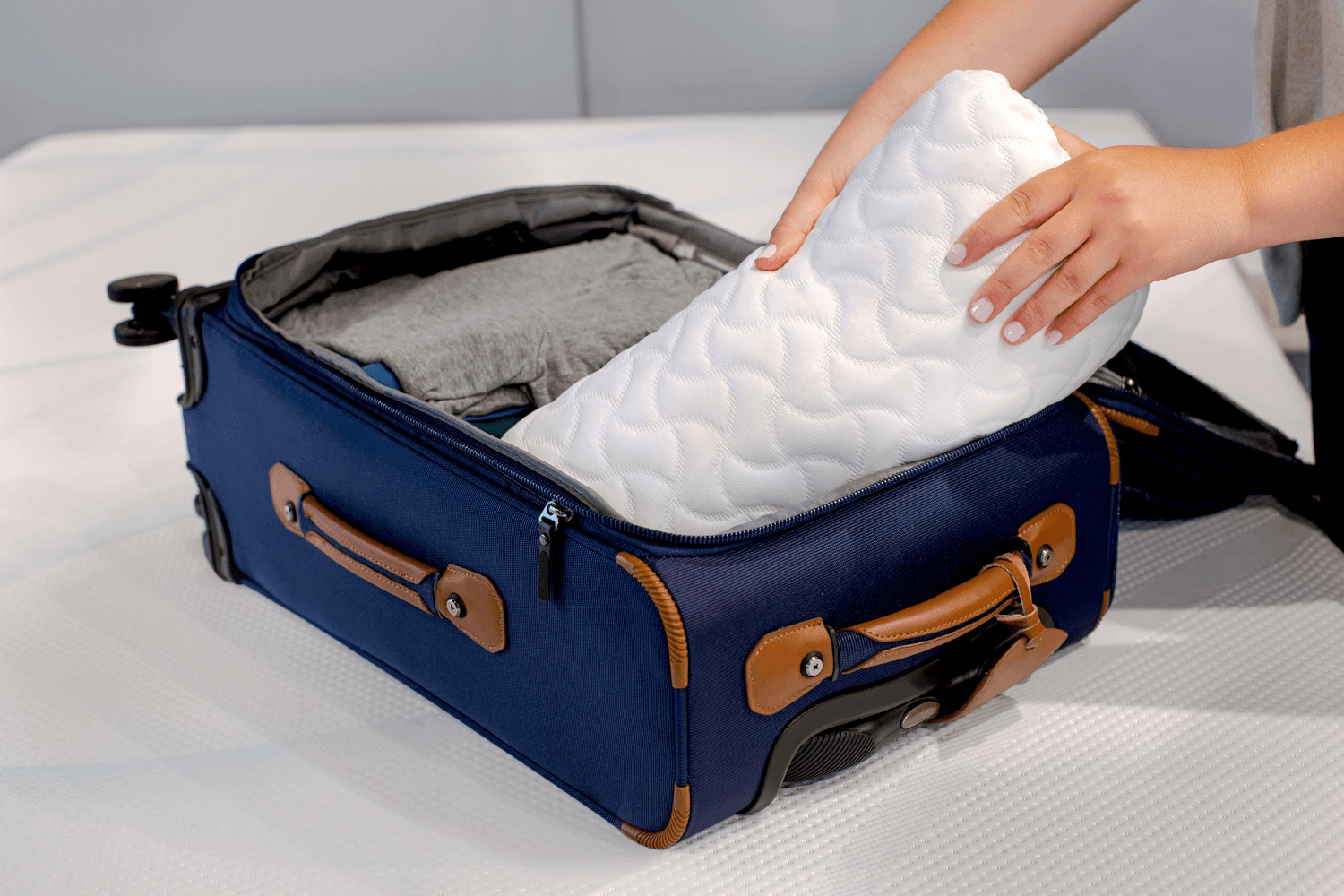 A rolled Tempur-Cloud pillow being packed into a travel bag