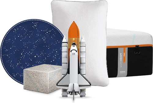 A tempur-pedic mattress, pillow, block of memory foam and spaceship arranged together