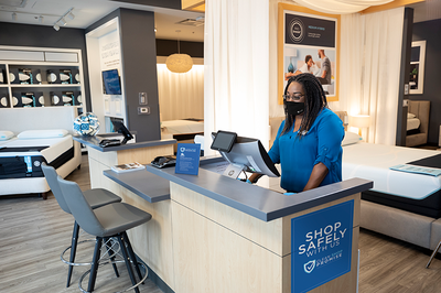 Woman with face mask standing behind cash register
