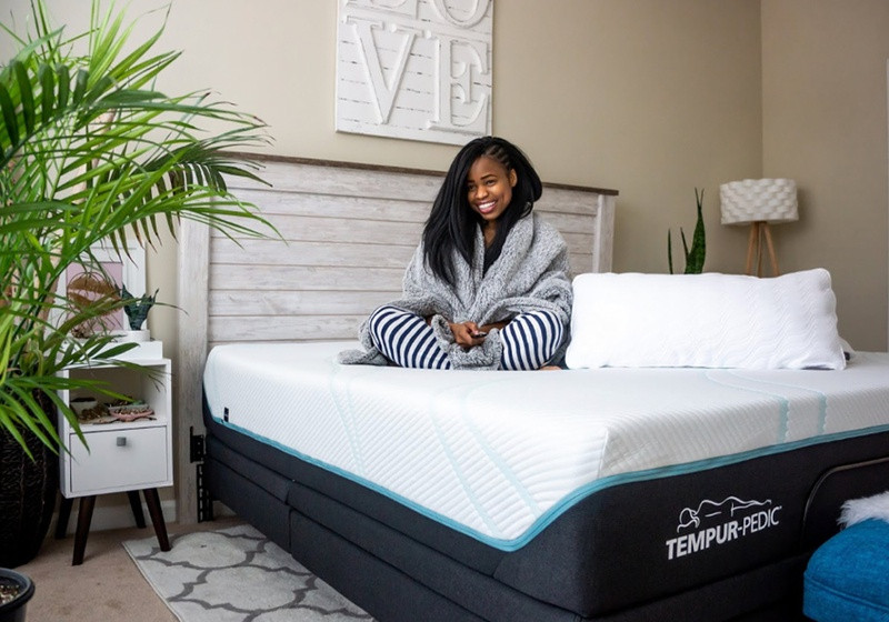 A smiling woman sitting on a Tempur-Pedic Mattress