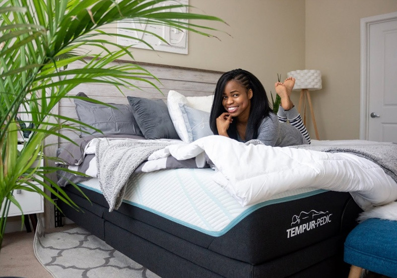 A smiling woman on a Tempur-Pedic mattress