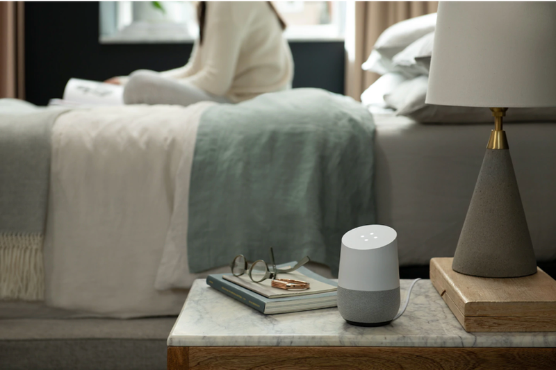 Google Home sitting on woman's nightstand