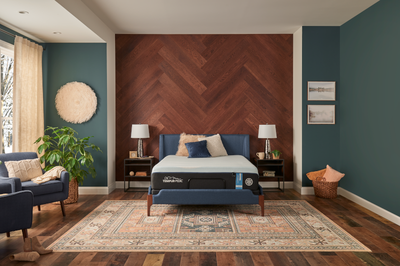 LuxeBreeze mattress in decorated room with herringbone wooden wall, decorative chairs, and an antique rug