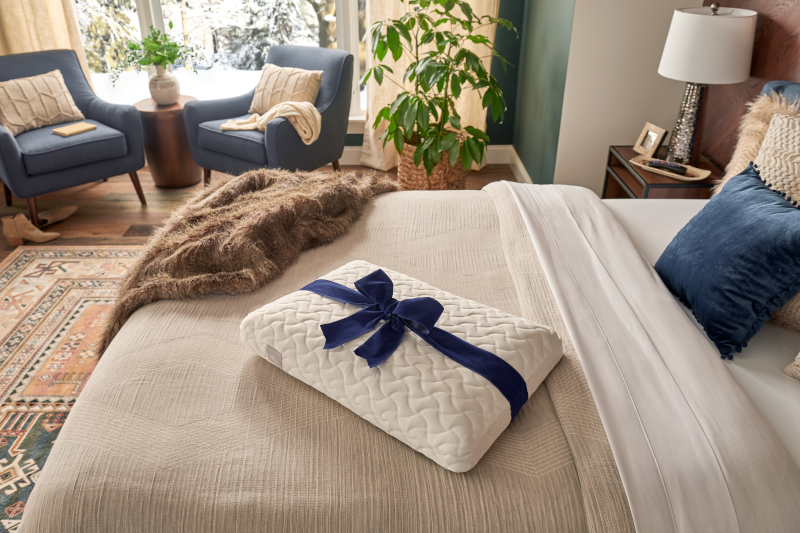 Tempur cloud pillow sitting on dressed bed with two blue chairs in the background.png