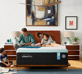 A happy family sitting on a TEMPUR-breeze mattress