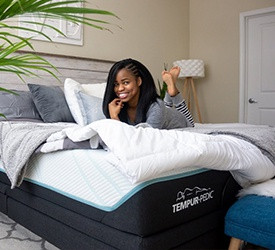 A smiling woman lying on a Tempur-Pedic mattress