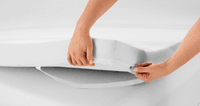 The corner of a mattress topper held up to show a strap underneath