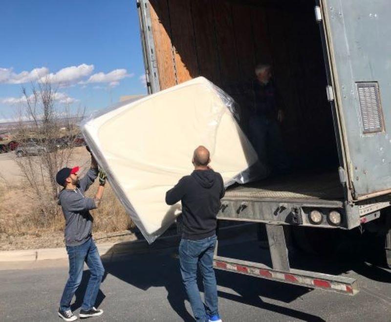 Two men unloading mattress from truck