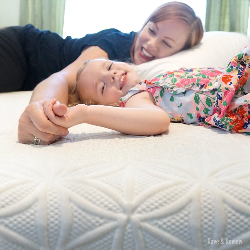 Woman and child lying on mattress holding hands and smiling