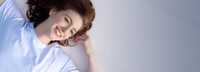A close up view of a smiling woman laying on the tempur-cloud mattress