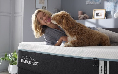Woman on Bed with Dog Licking Face.png