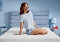 A laughing woman posing on a Tempur-Cloud mattress in a well lit room