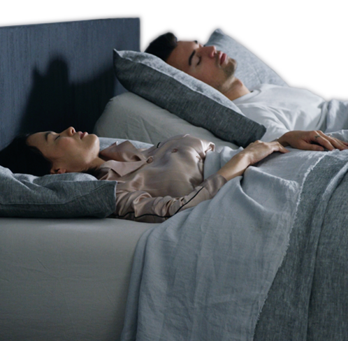 A couple sleeping with the man slightly elevated using the automatic snore response feature.