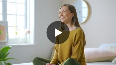 woman sitting on mattress smiling